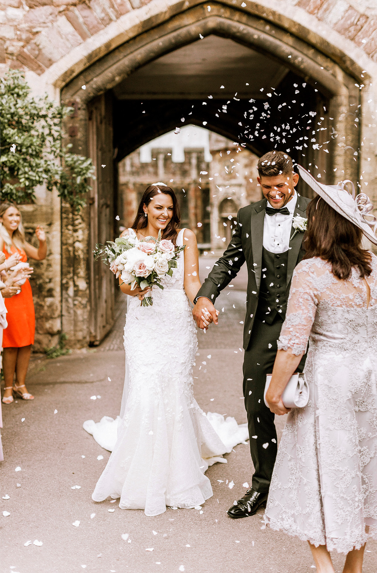 bride and groom holding hands during ceremony while being showered with confetti