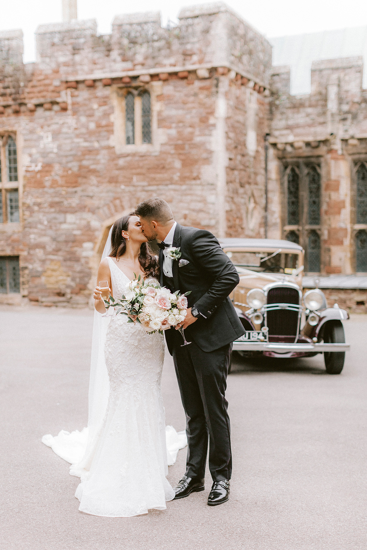 couple kissing while holding champaign in front of caste and antique car