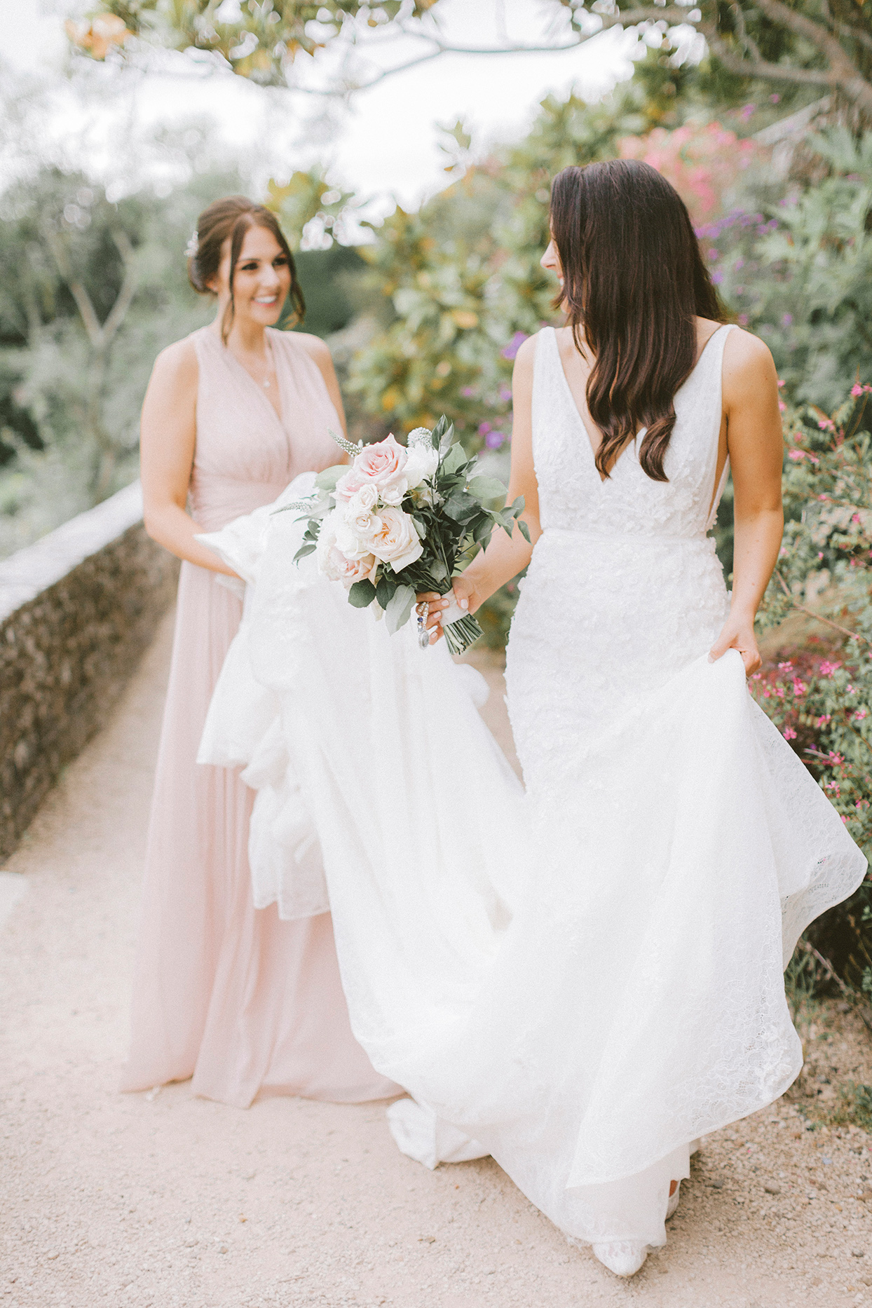 bridesmaid holding up bride's dress train on gravel path