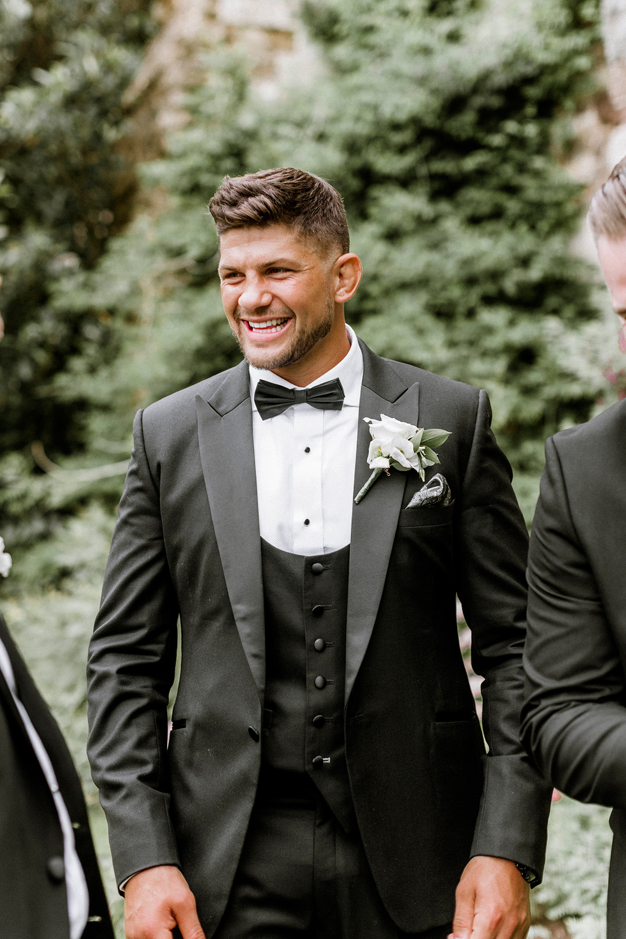 groom smiling in black wedding tux with bowtie