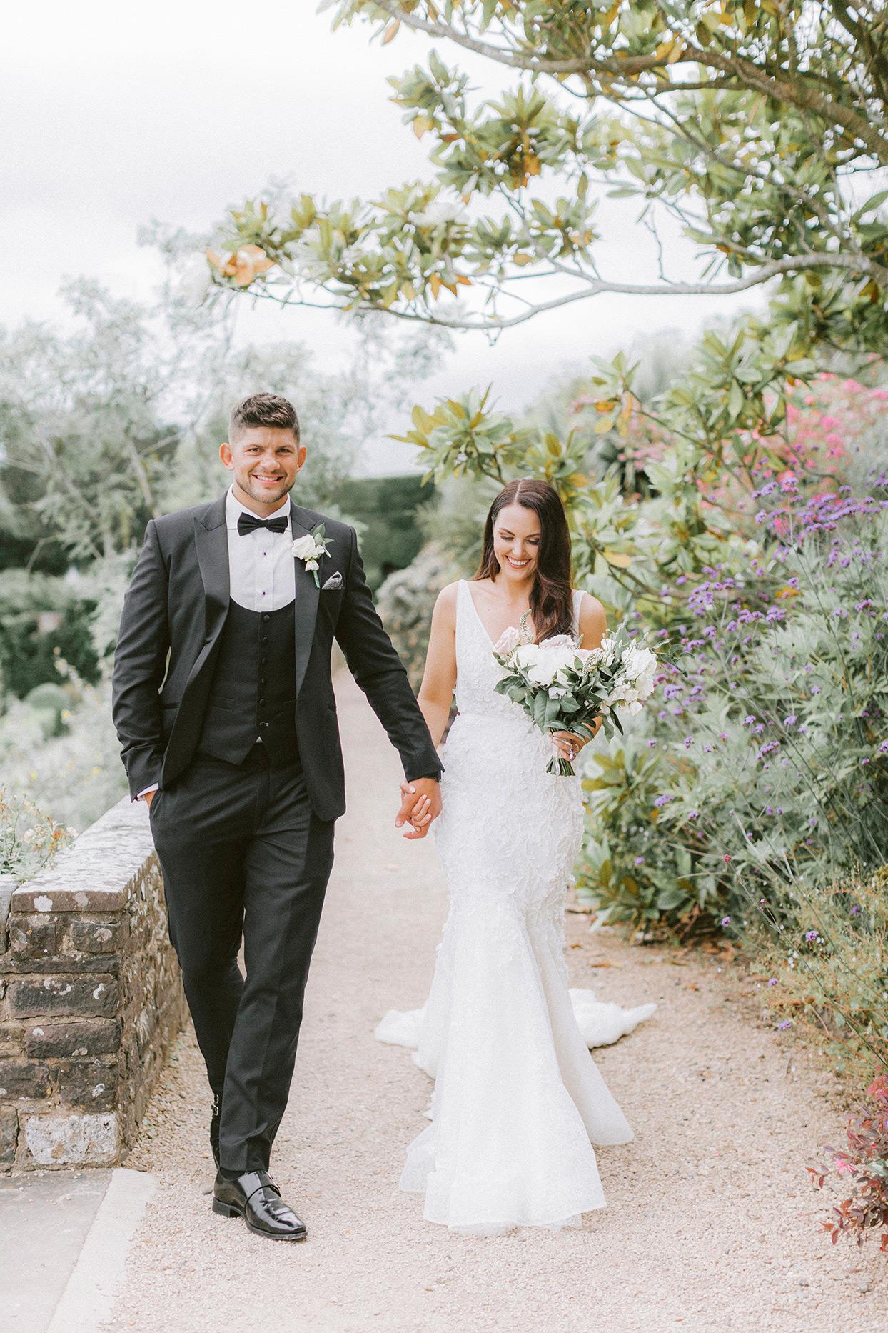 bride and groom walking along gravel path in garden