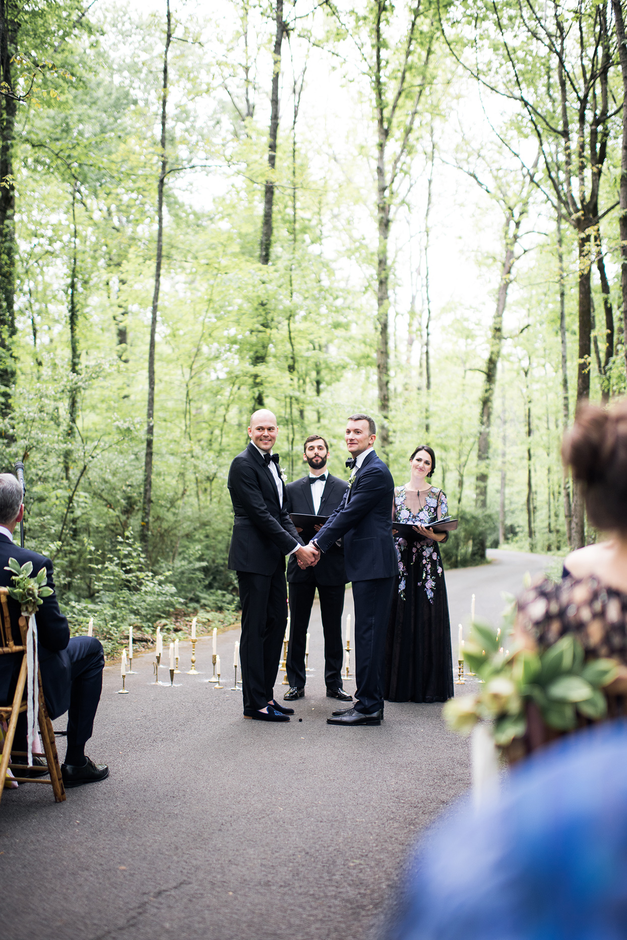 grooms holding hands during forest ceremony
