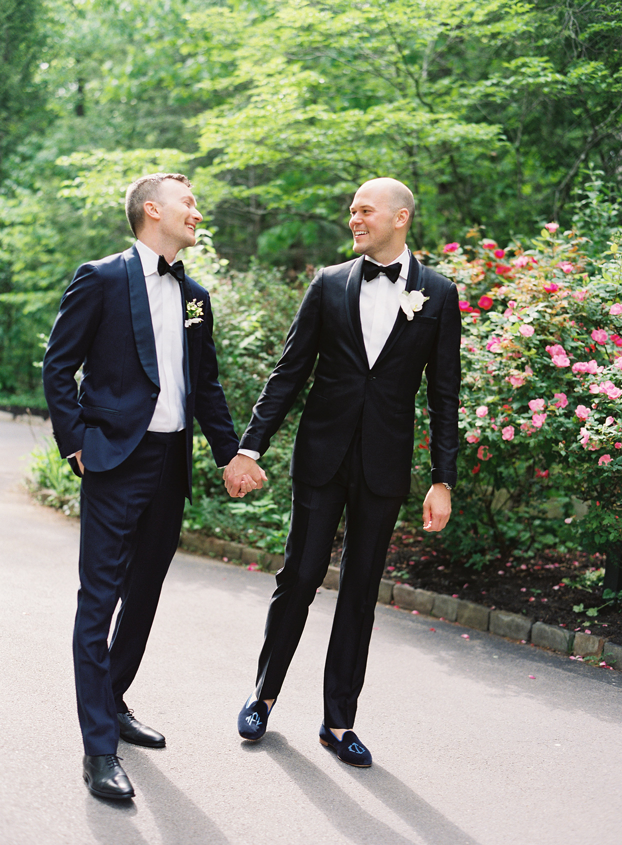 wedding grooms holding hands during portraits
