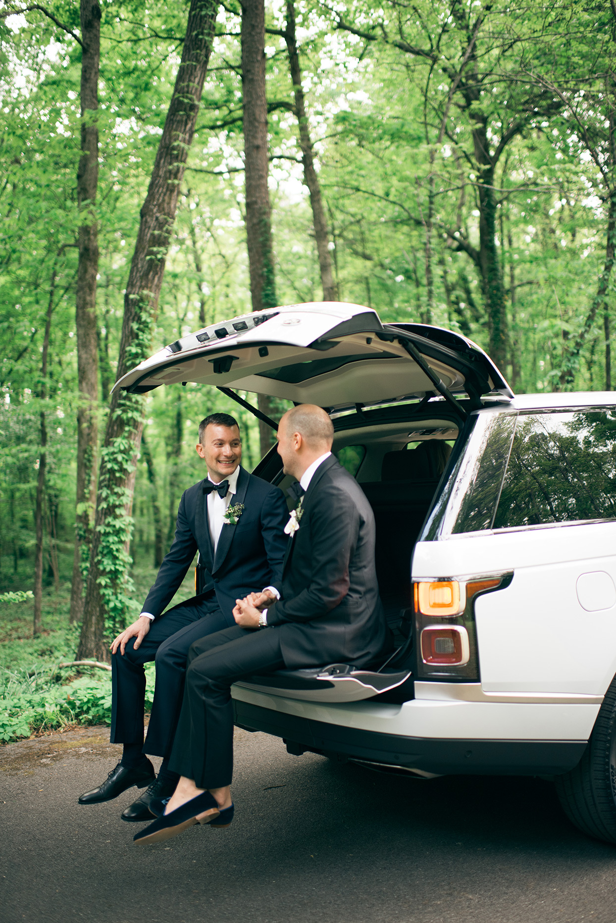 grooms sitting inside open tailgate of car in the forest