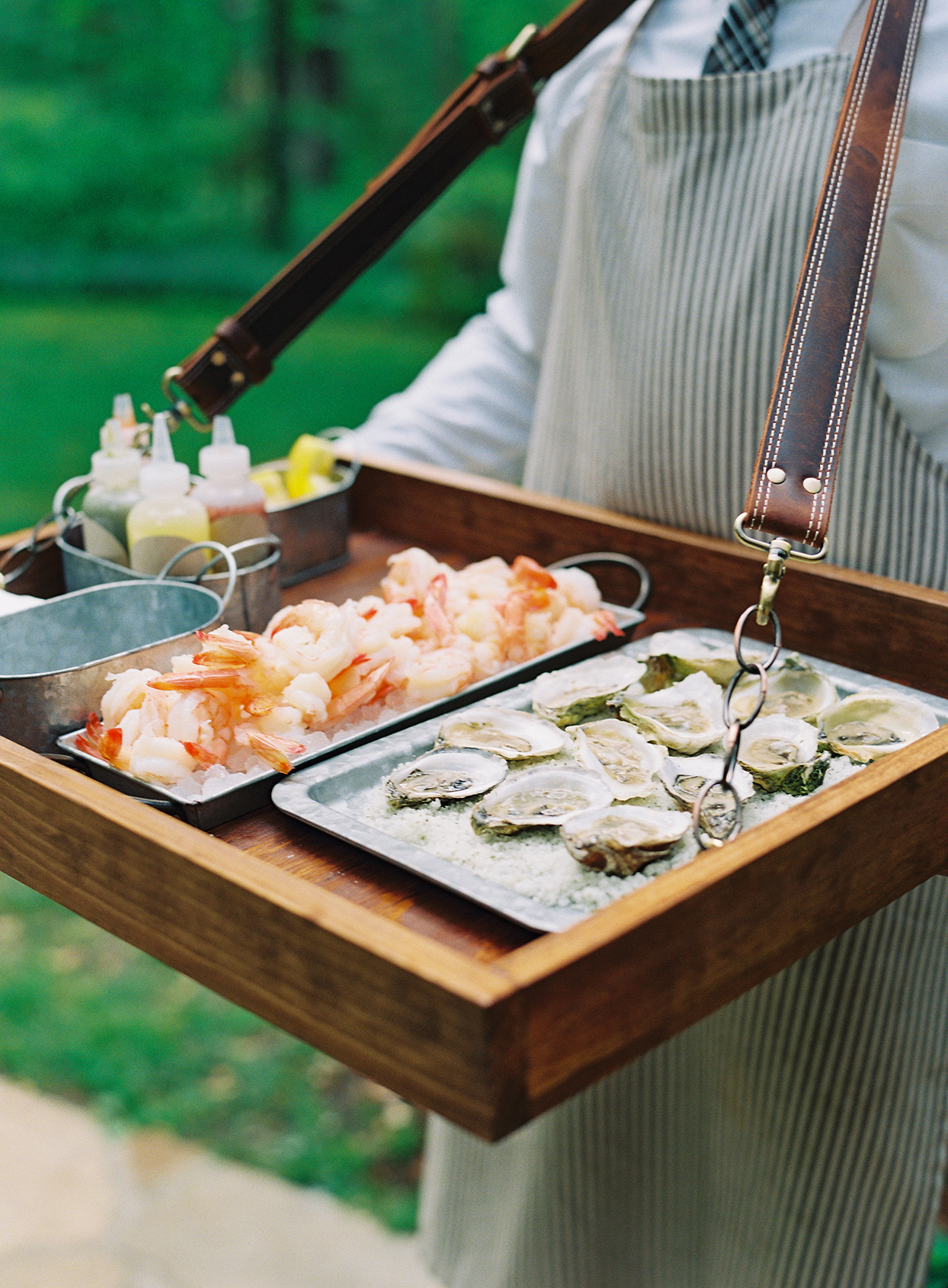 server carrying wedding appetizers of shrimp and oysters
