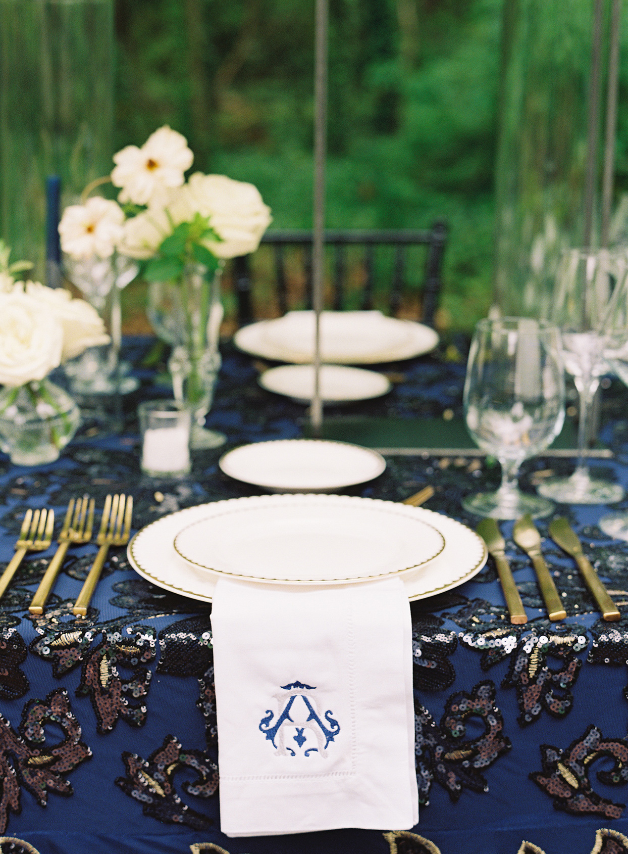 white, blue and gold place setting with monogrammed napkin