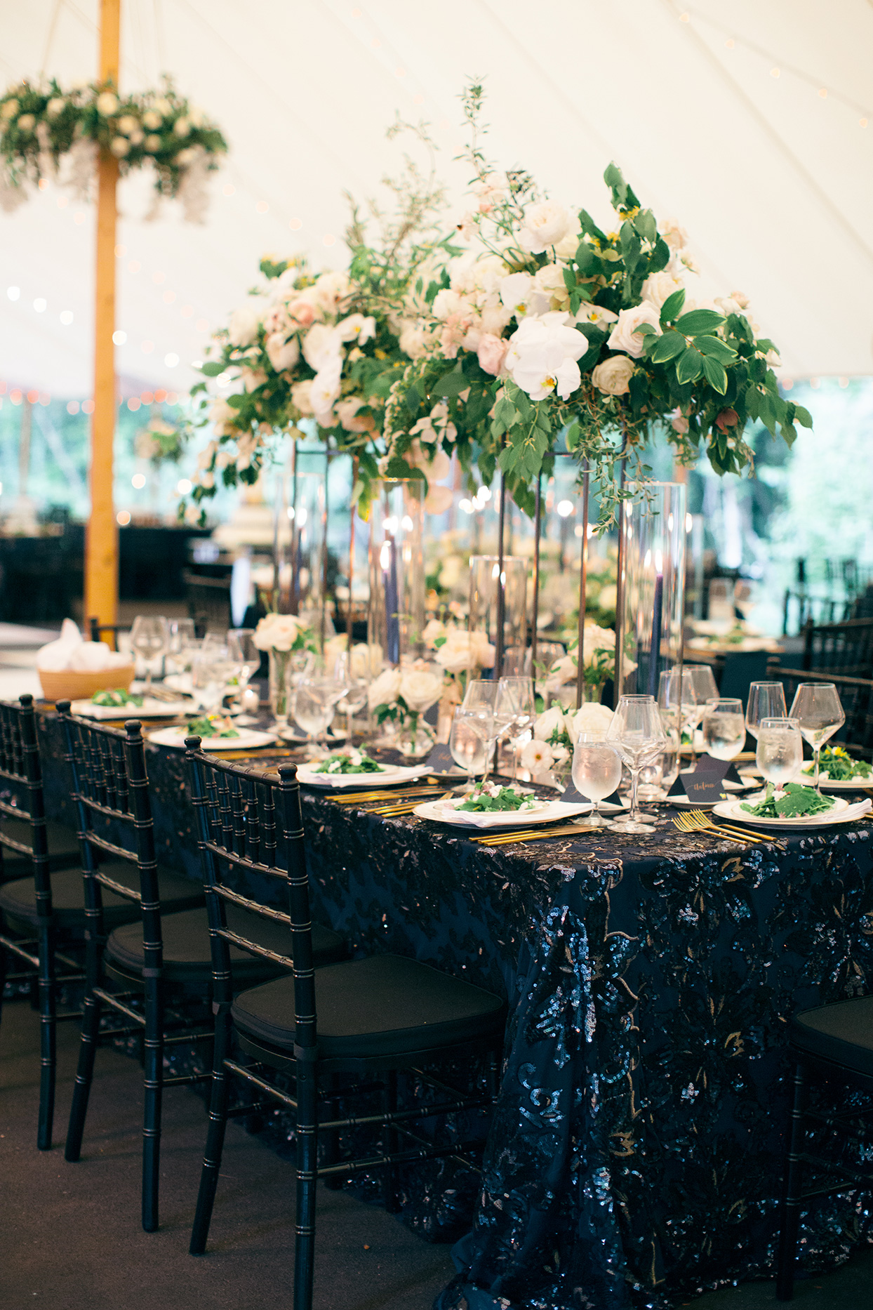 reception tables with shimmering blue tablecloths and tall centerpieces