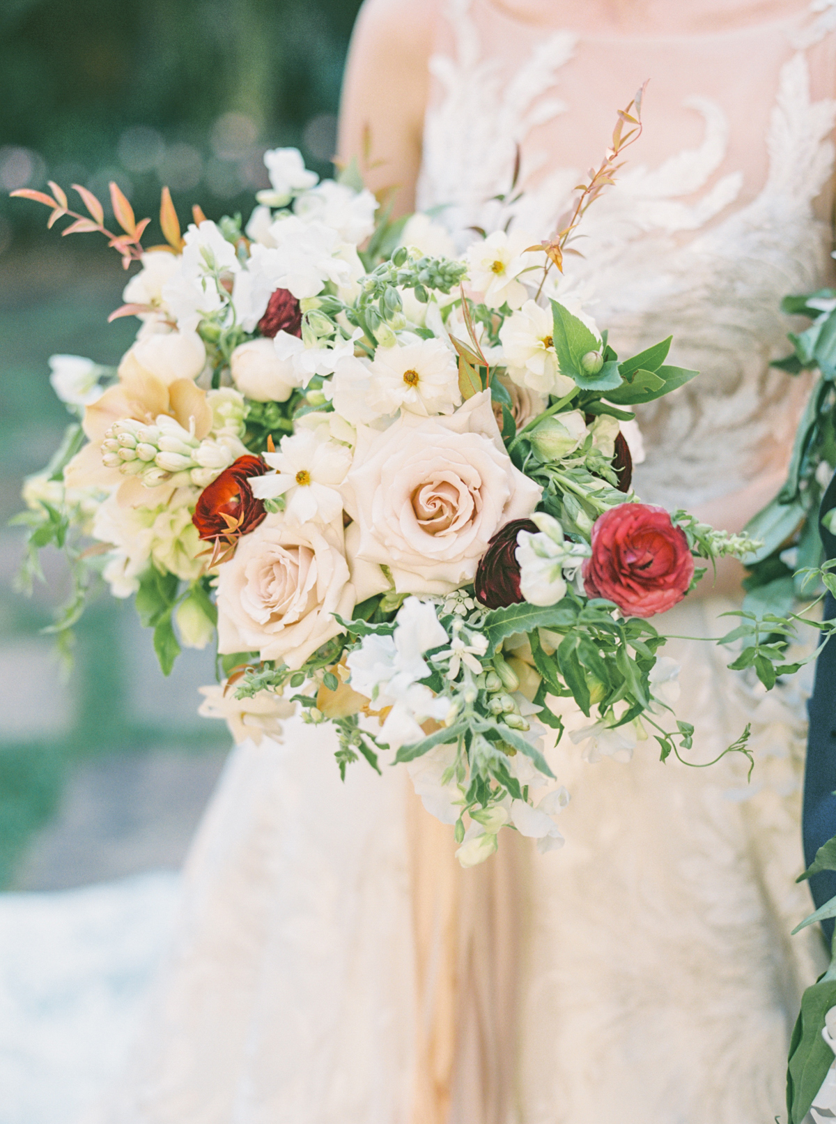 bride holding mauve, maroon and neutrals wedding bouquet