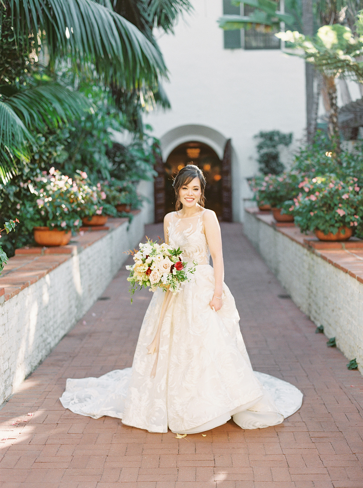bride in cream dress standing in courtyard