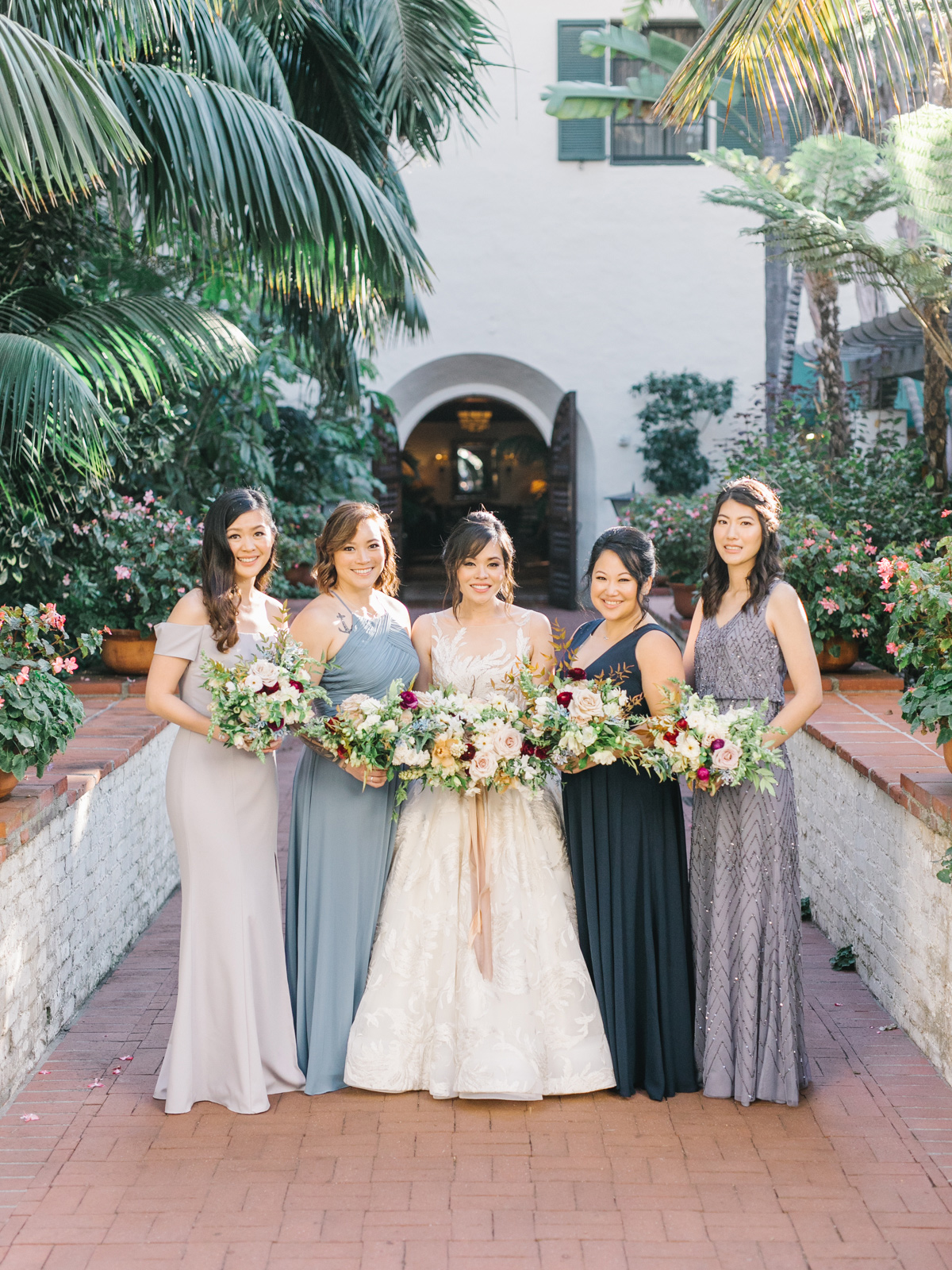 bride and bridesmaids in shades of blue in courtyard