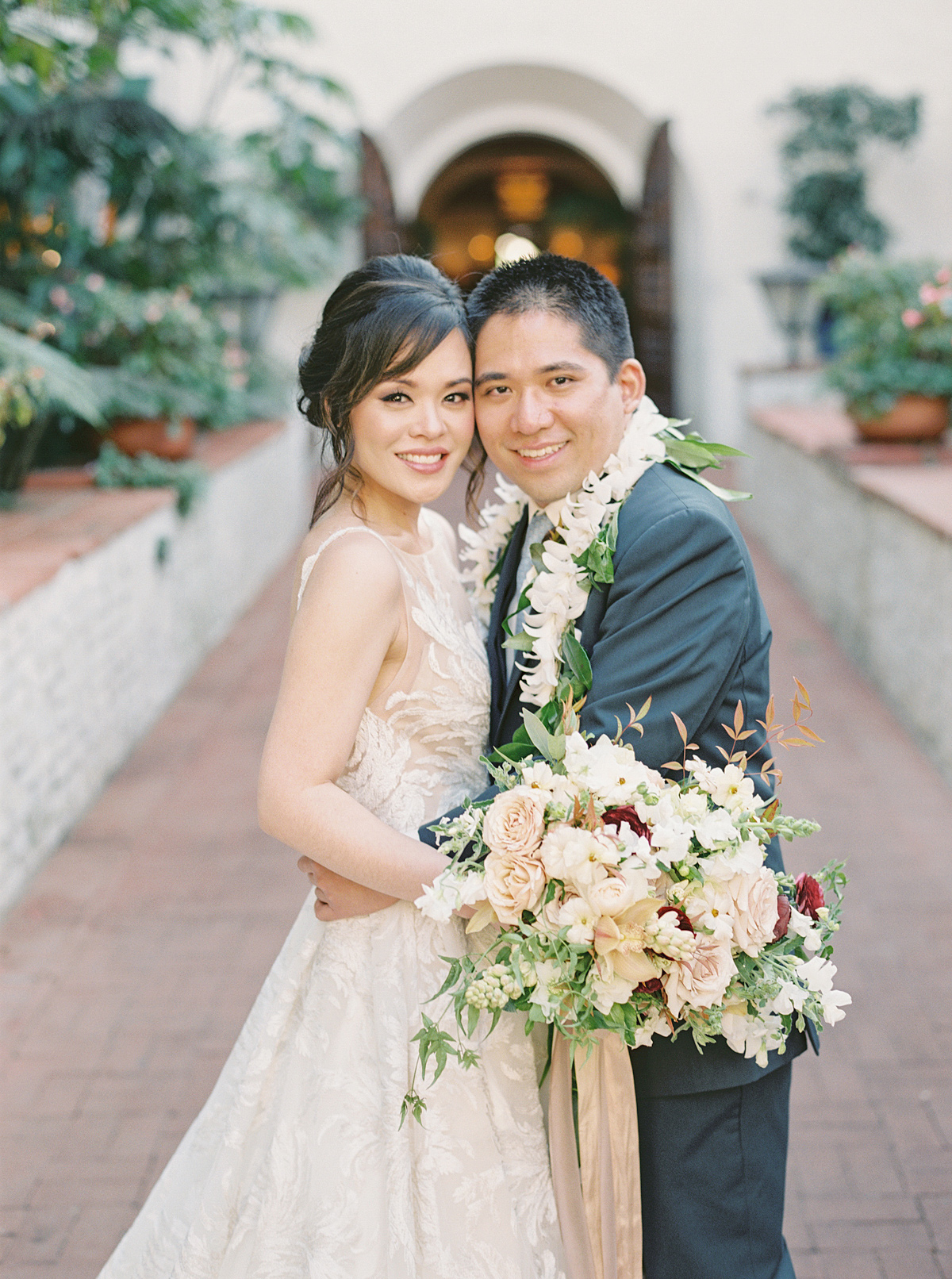 wedding couple hugging for portrait in courtyard