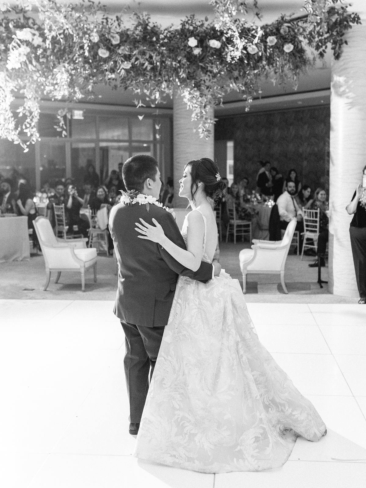 couple dancing at reception under floral installment