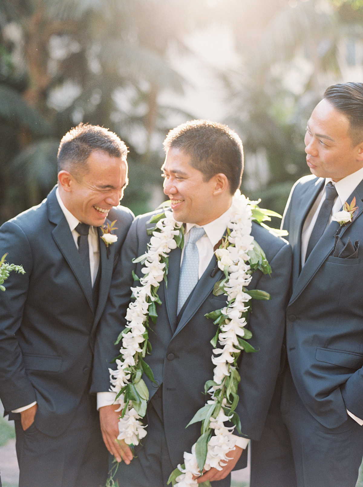 groomsmen laughing and smiling with groom wearing floral garland