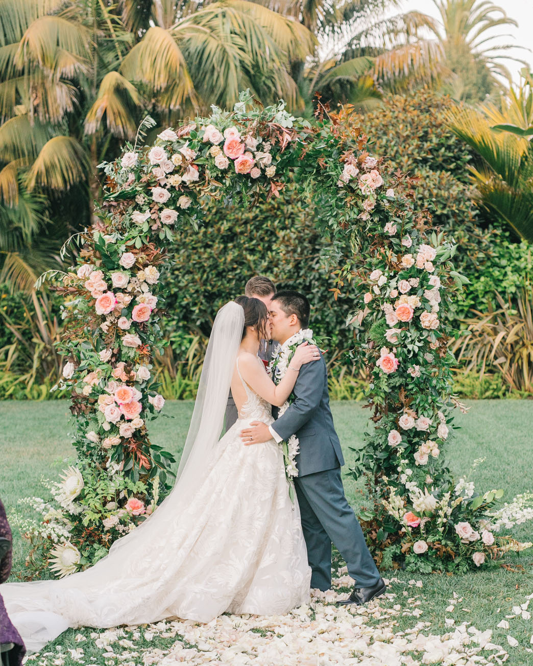 corey evan wedding couple kiss during ceremony under floral arch