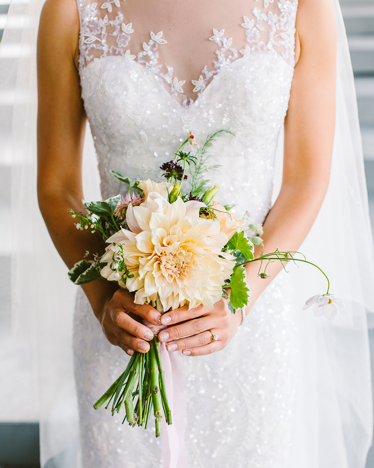 bride in white holding pastel bouquet with orange flower