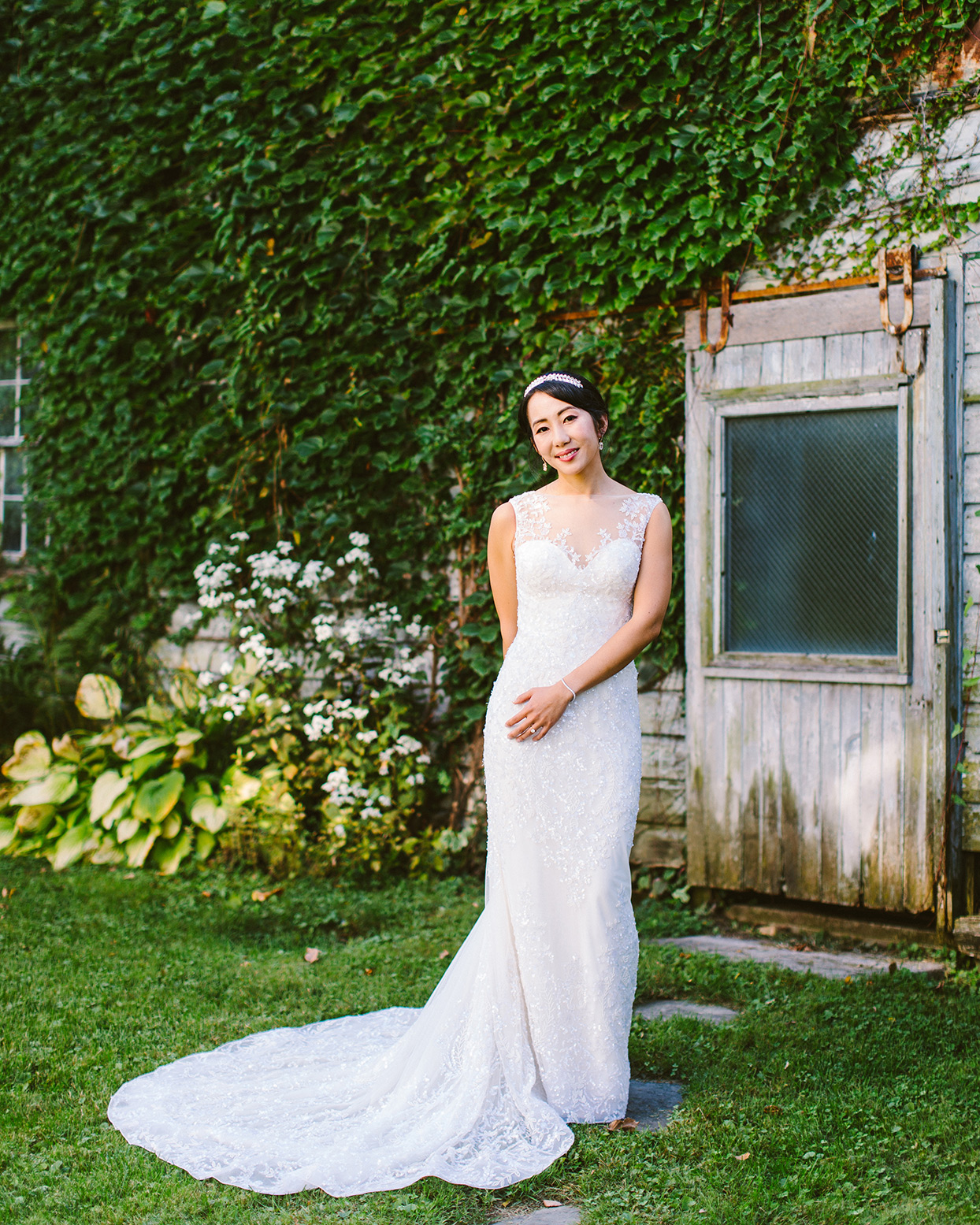 bride in white dress standing on stone path in the grass