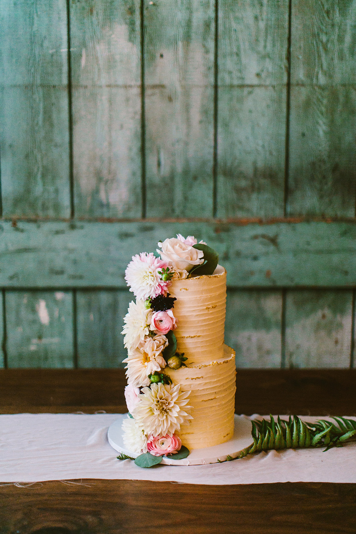 rustic orange wedding cake with flowers down the side