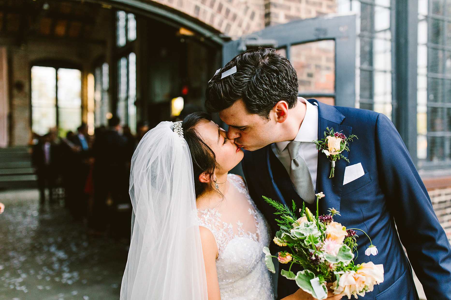wedding couple kissing outside industrial ceremony space