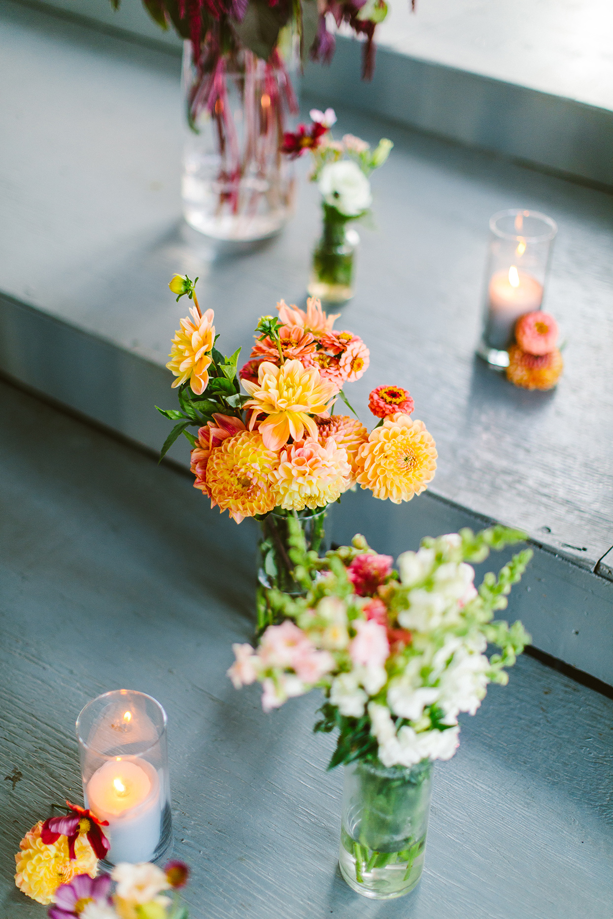 orange and pink flowers on rustic steps during wedding ceremony
