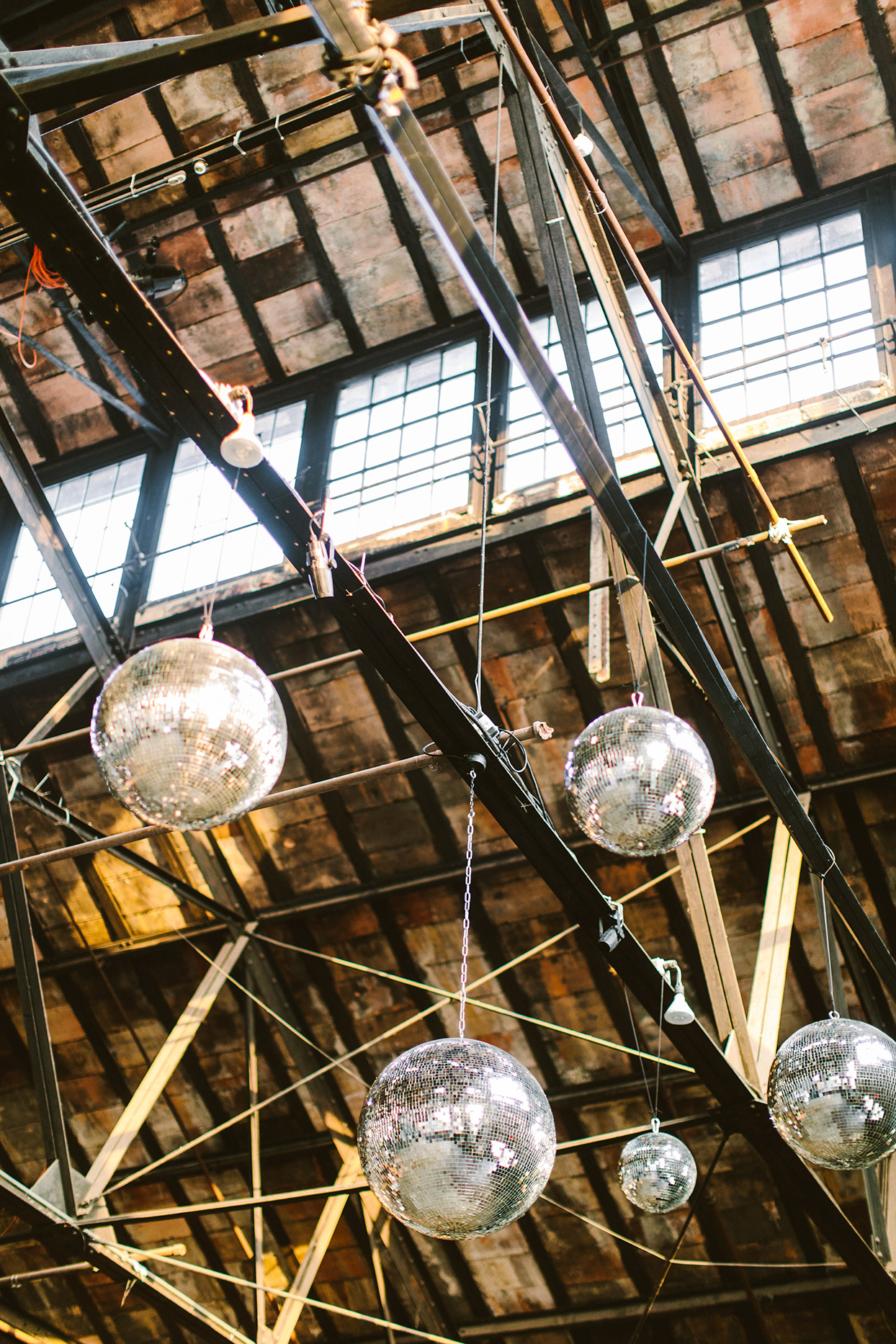 wedding disco balls hanging from industrial rafters