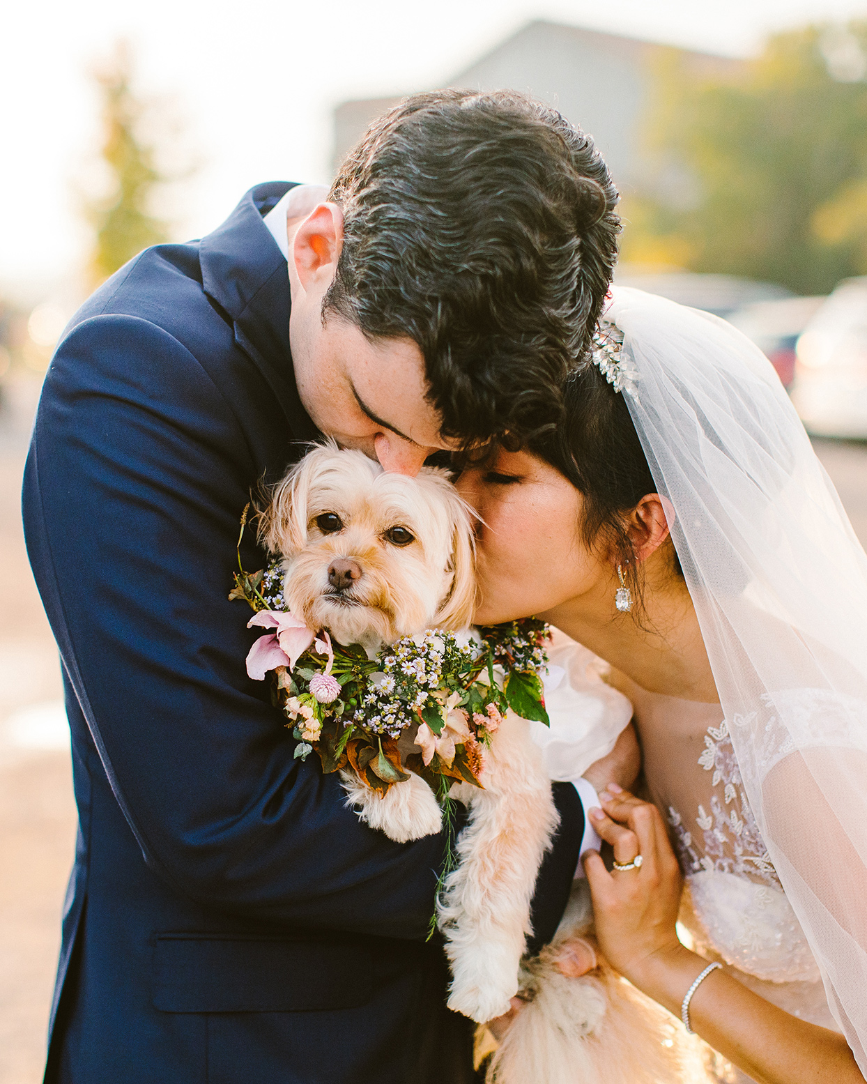wedding couple embracing dog wearing floral wreath