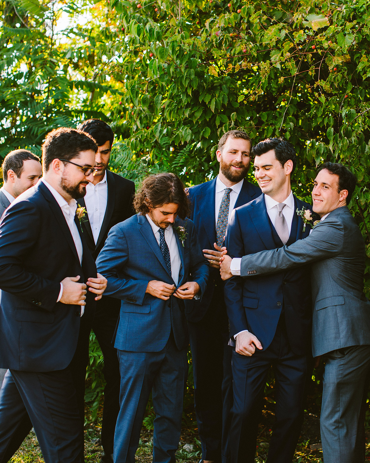 groomsmen adjusting suits in front of greenery