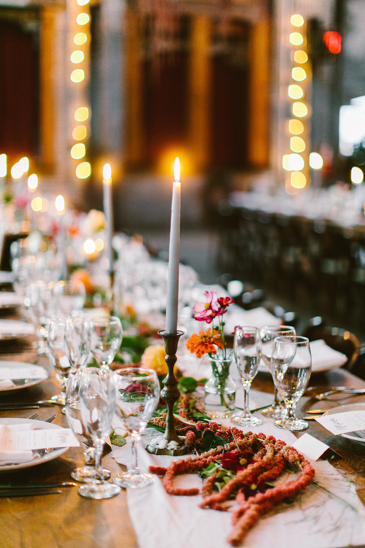 close up of wedding long table centerpiece of red flowers and candles