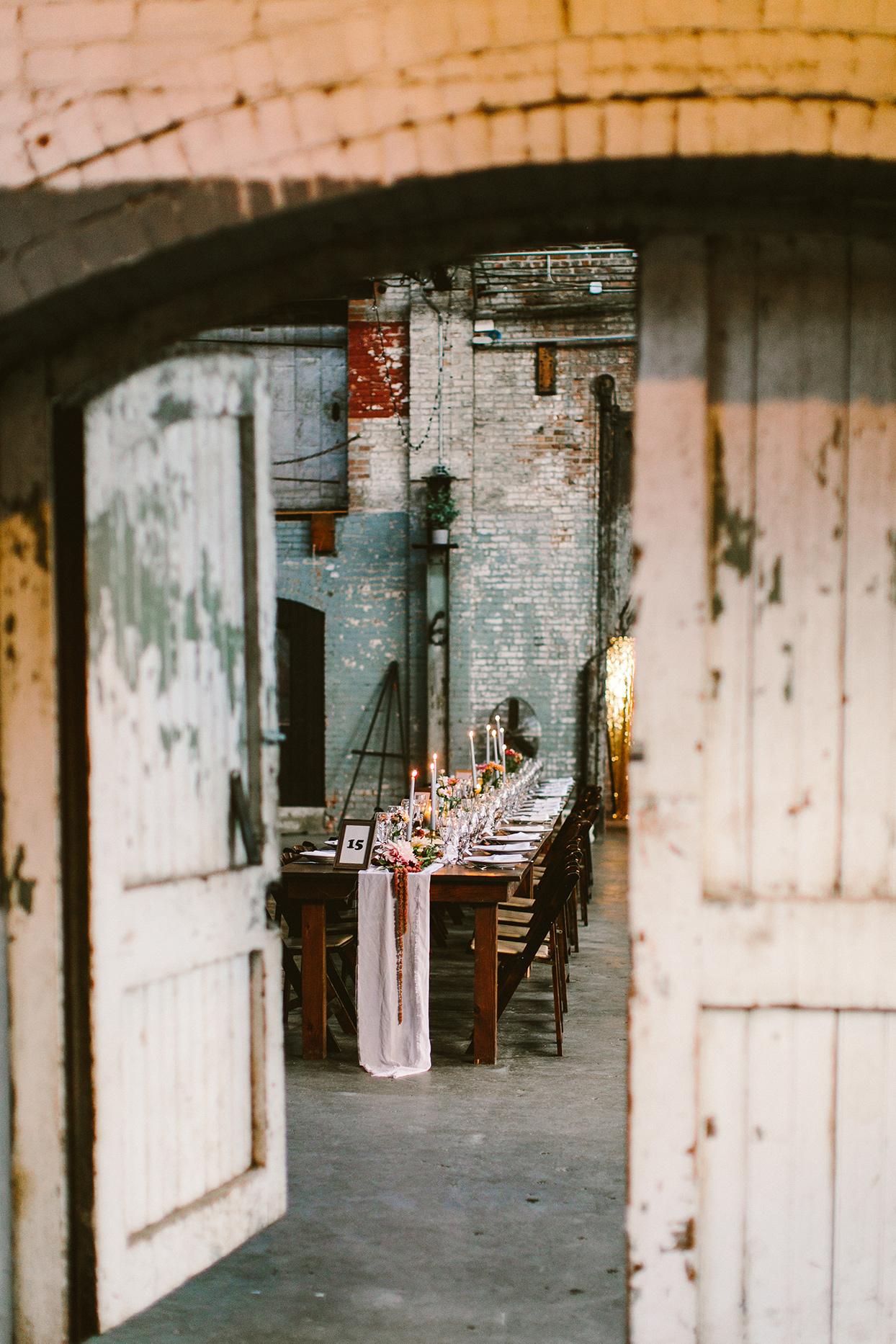 rustic barn doors open to industrial wedding reception tables