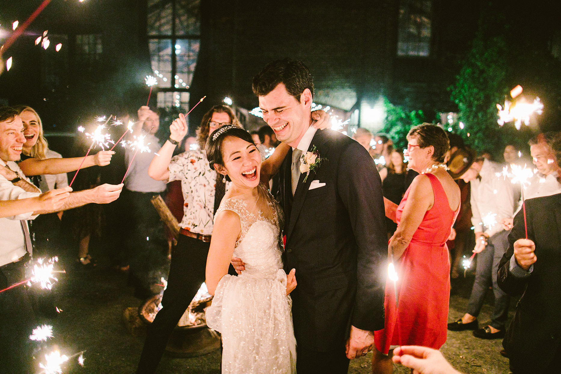 wedding couple laughing while guests hold sparklers around them