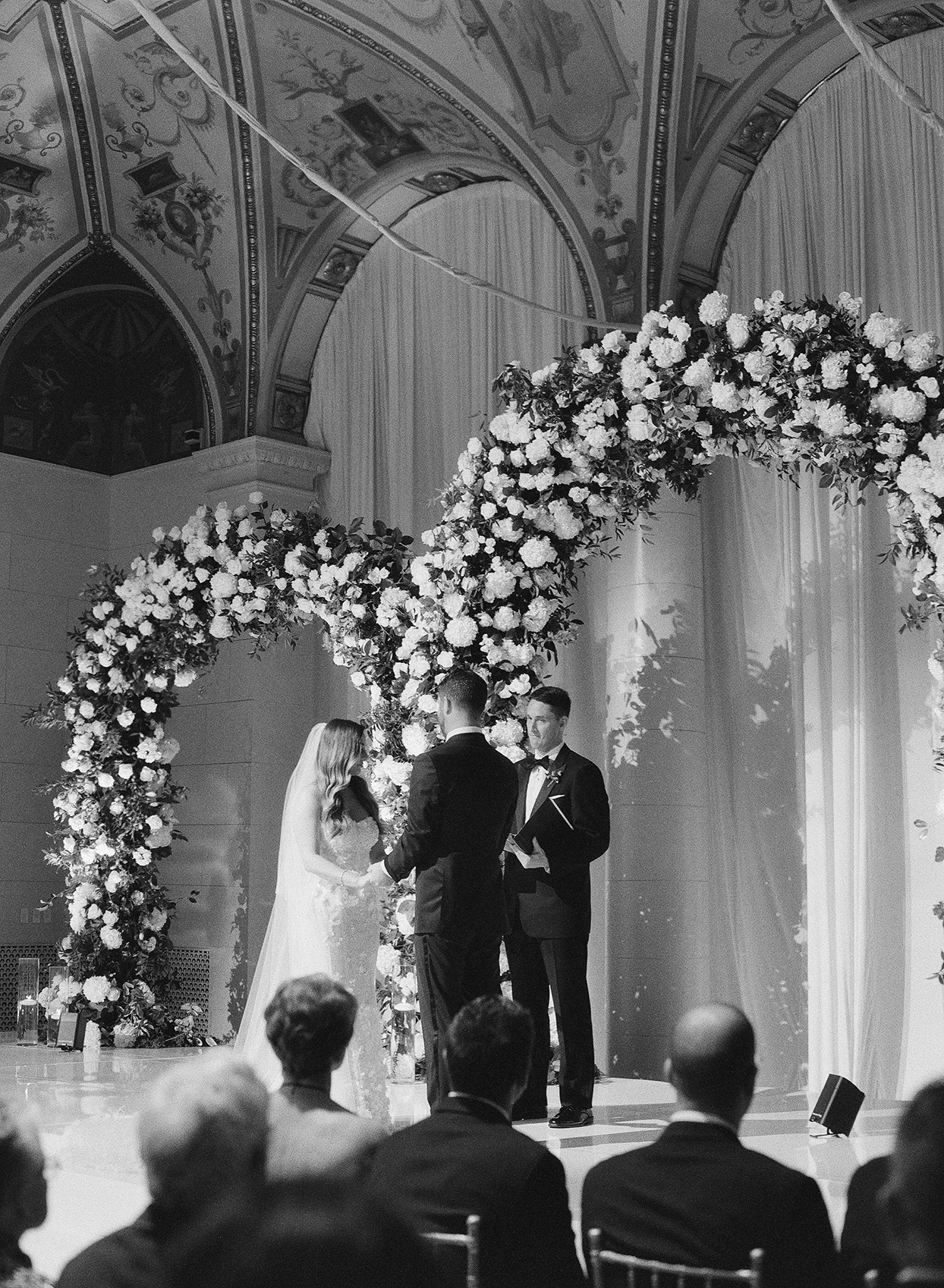 brittany brian wedding ceremony couple under floral arch