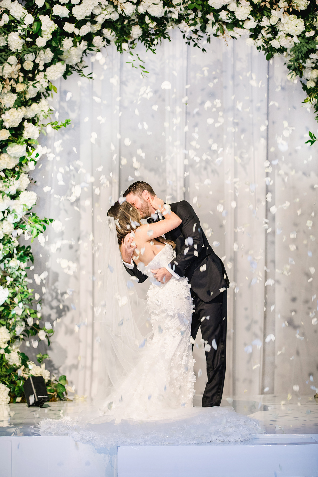 brittany brian wedding ceremony couple kissing under floral arch