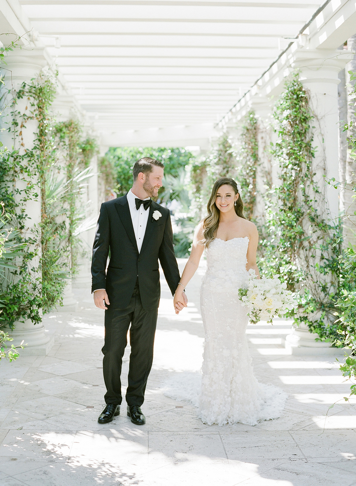brittany brian wedding couple walking through stone garden structure
