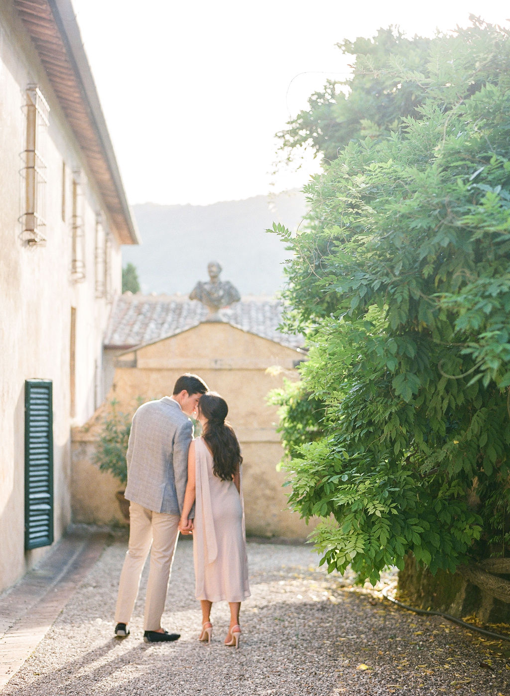 bride and groom holding hands and kissing on italian street