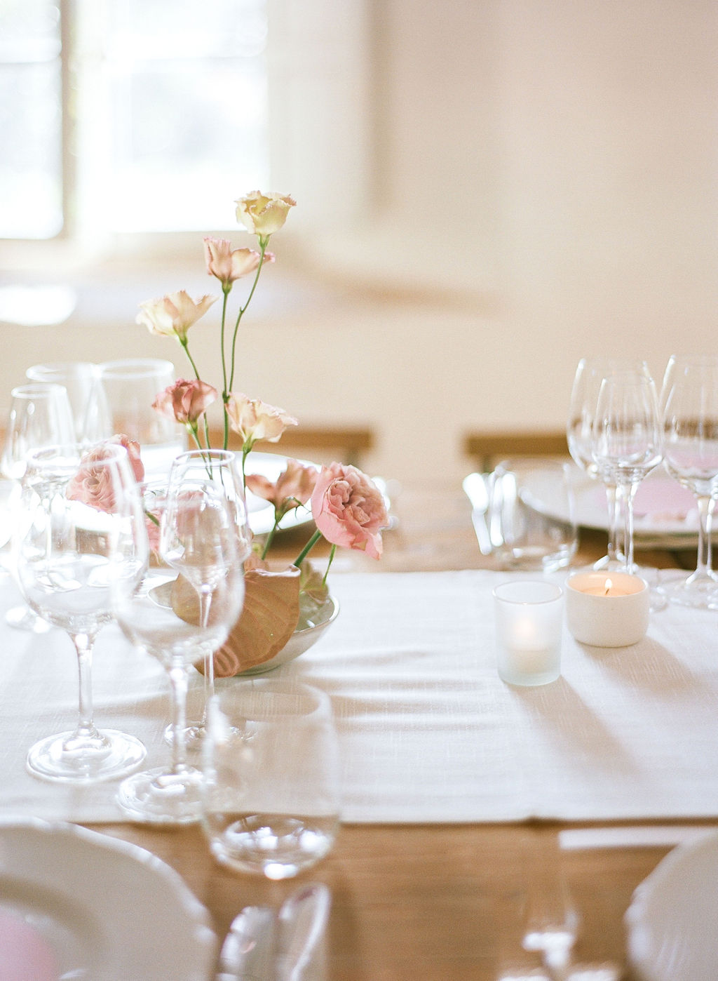 pink roses displayed on rehearsal dinner table