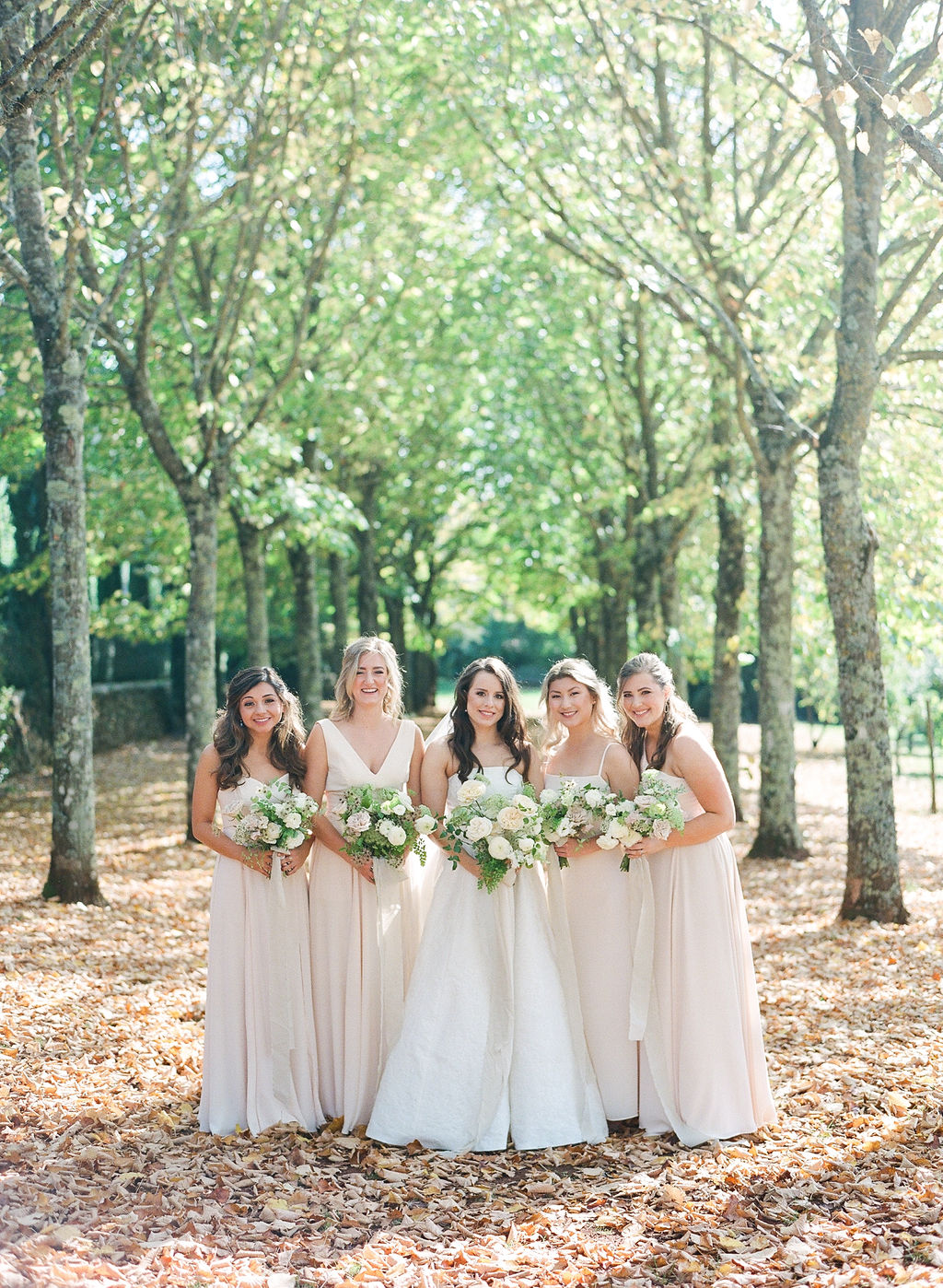 bride posing with bridesmaids surrounded by trees