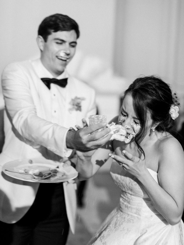 groom smashing wedding cake onto brides face