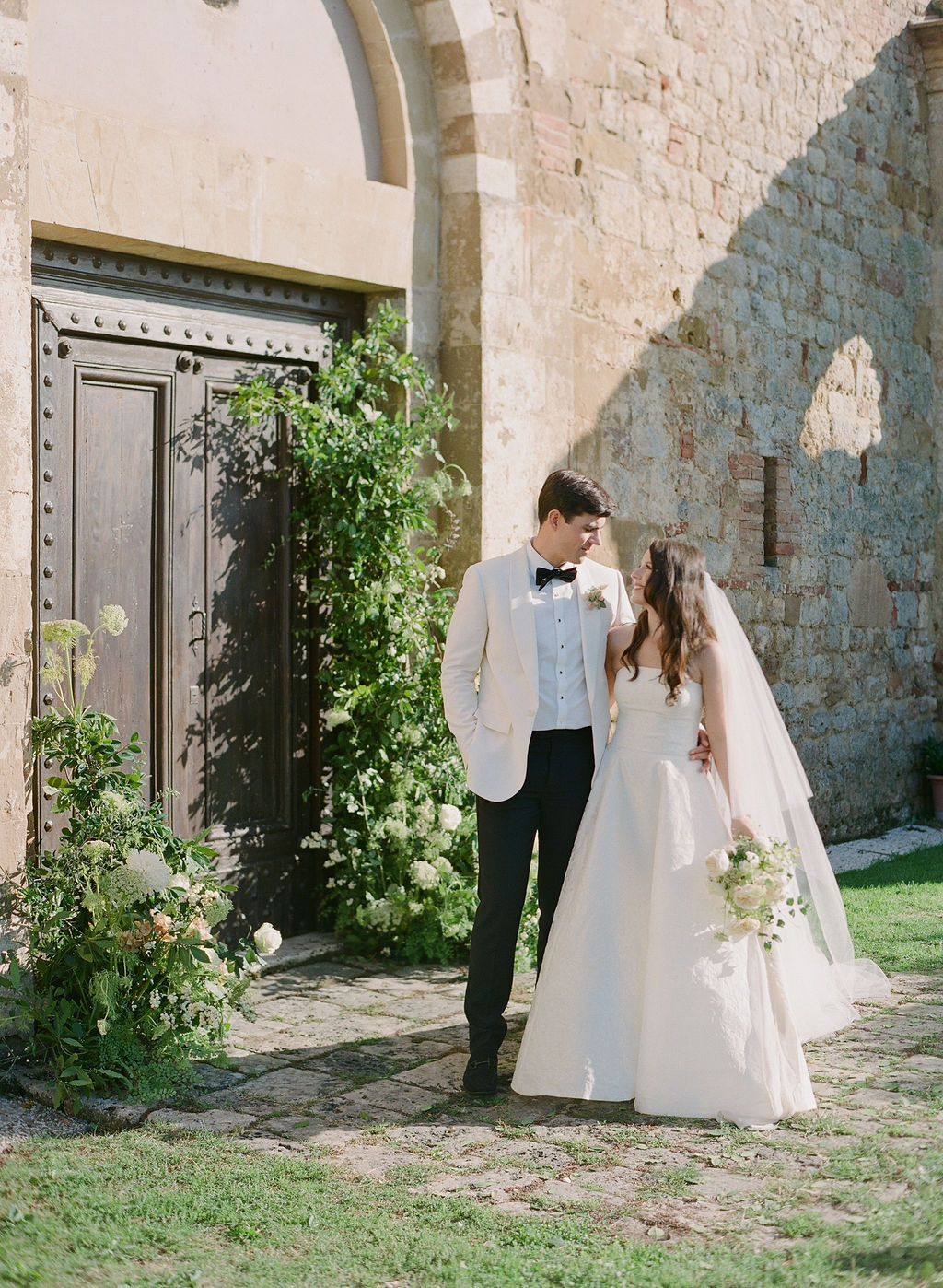 bride and groom smiling in front of italian church portal