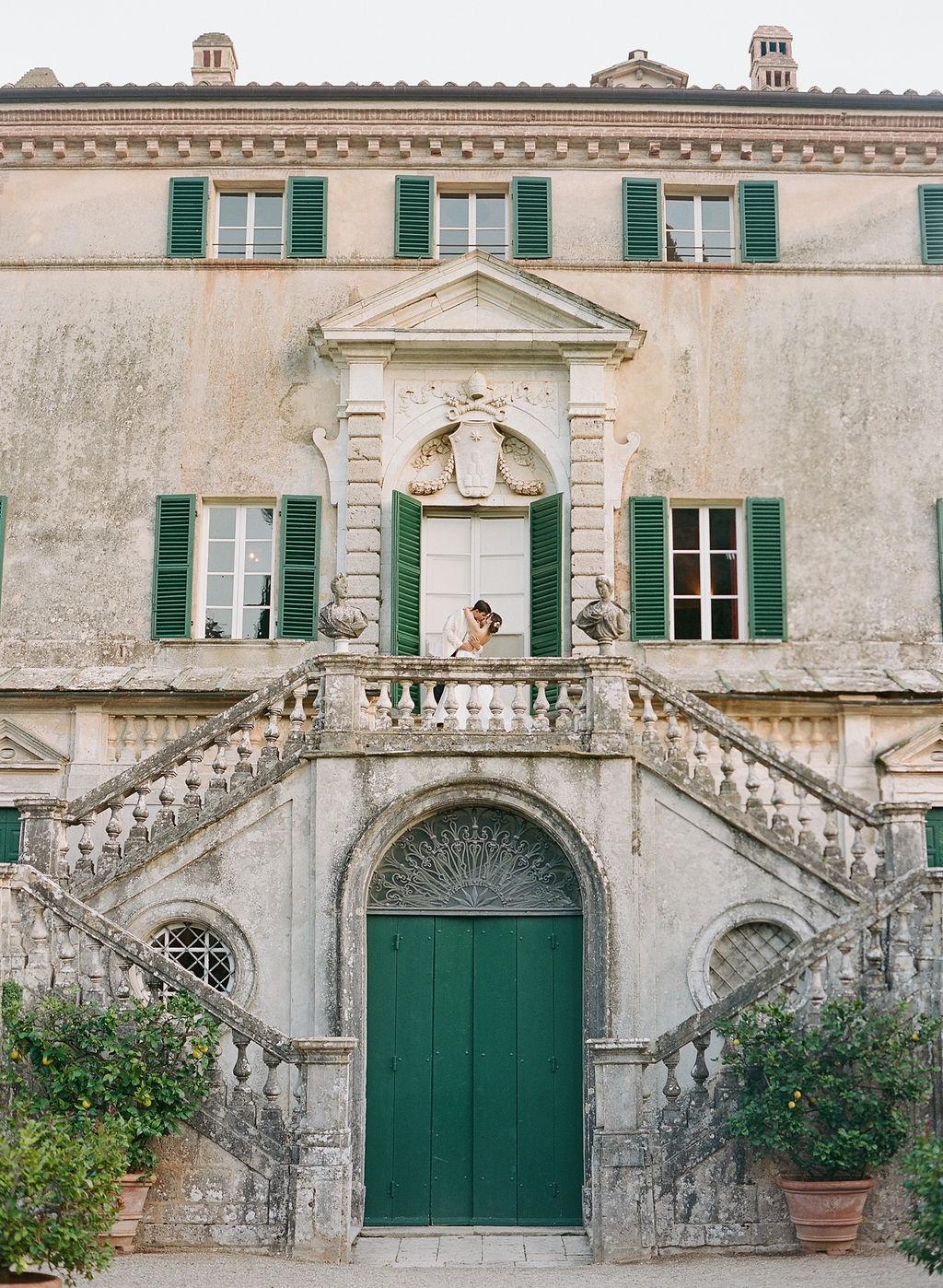 bride and groom kissing on italian balcony