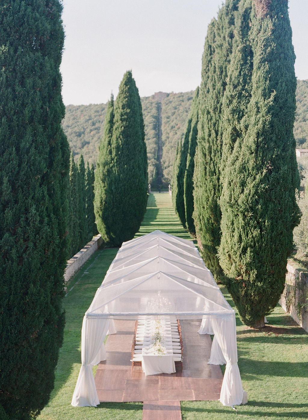 one long table between two rows of cypress trees behind the villa