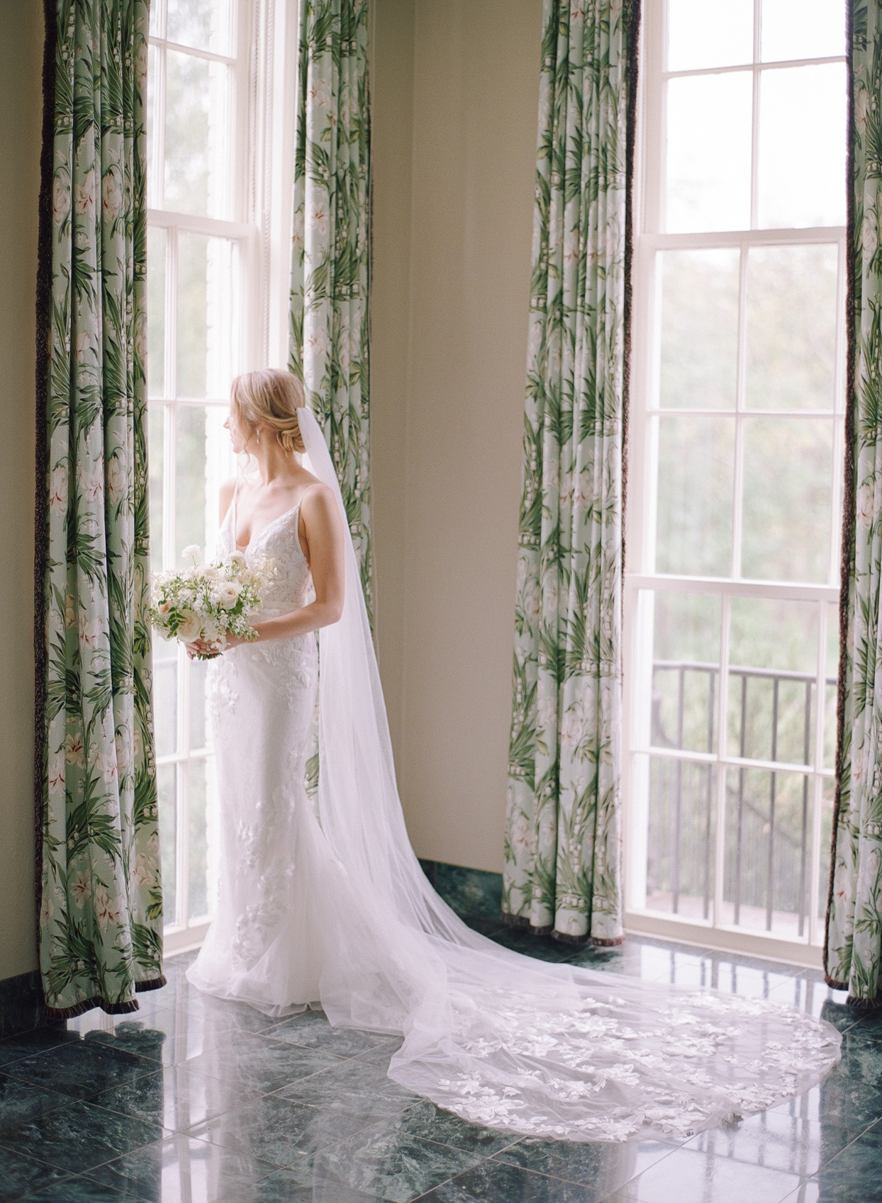 bride wearing long lace train, v-neck, thin strap wedding dress with veil
