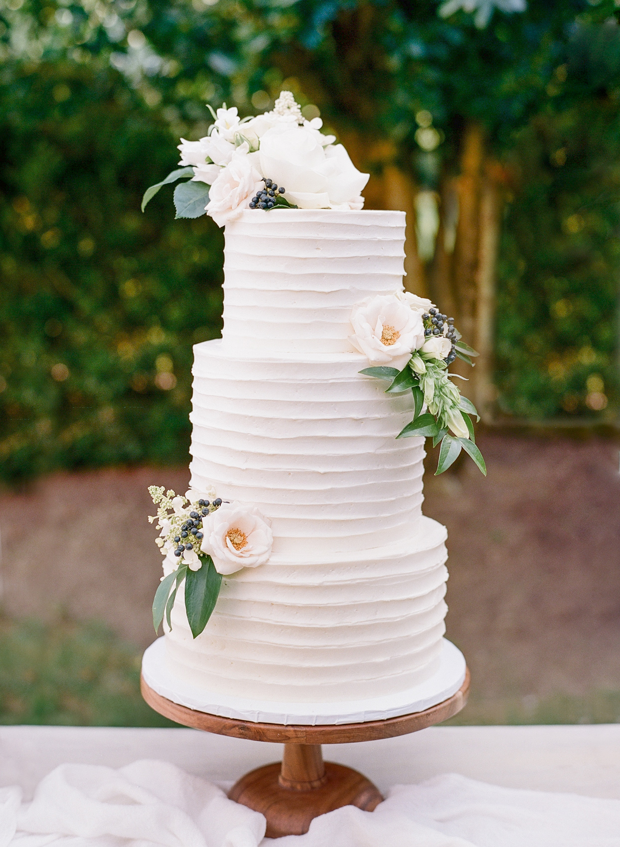 three tiered white frosted wedding cake with white floral accent decor
