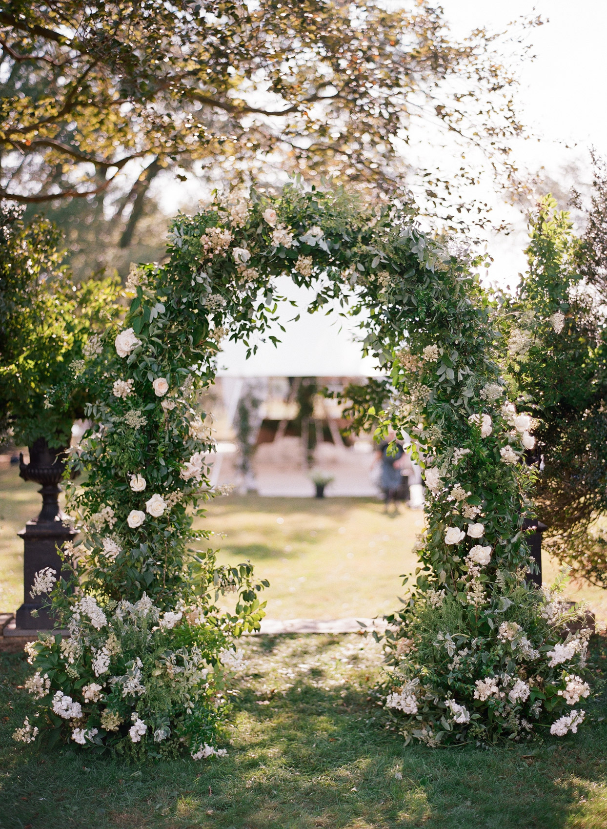 white floral and greenery wedding ceremony arch