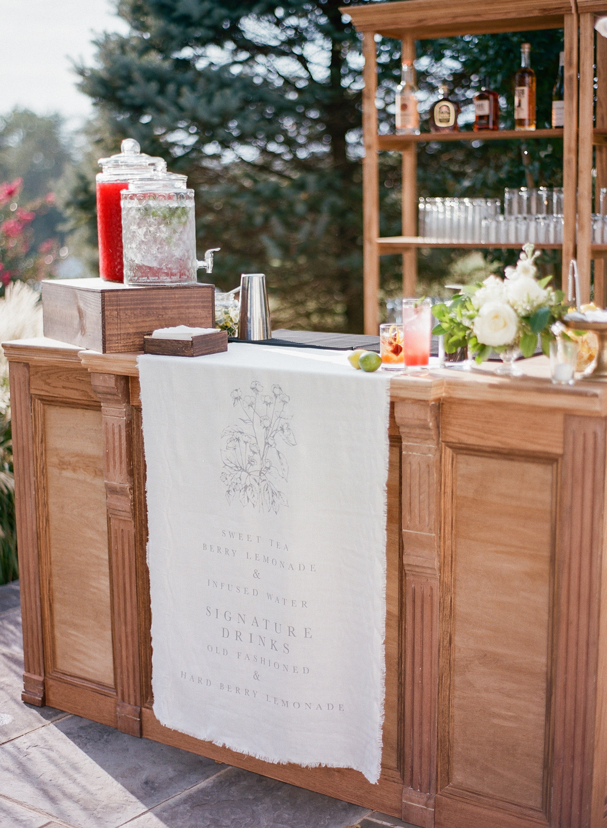 outdoor cocktail hour stand with white cloth cocktail sign