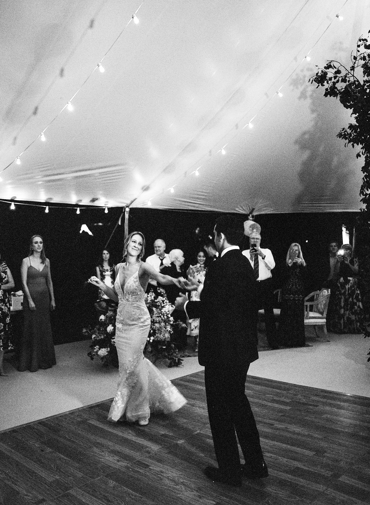 bride smiling at groom during first dance under reception tent