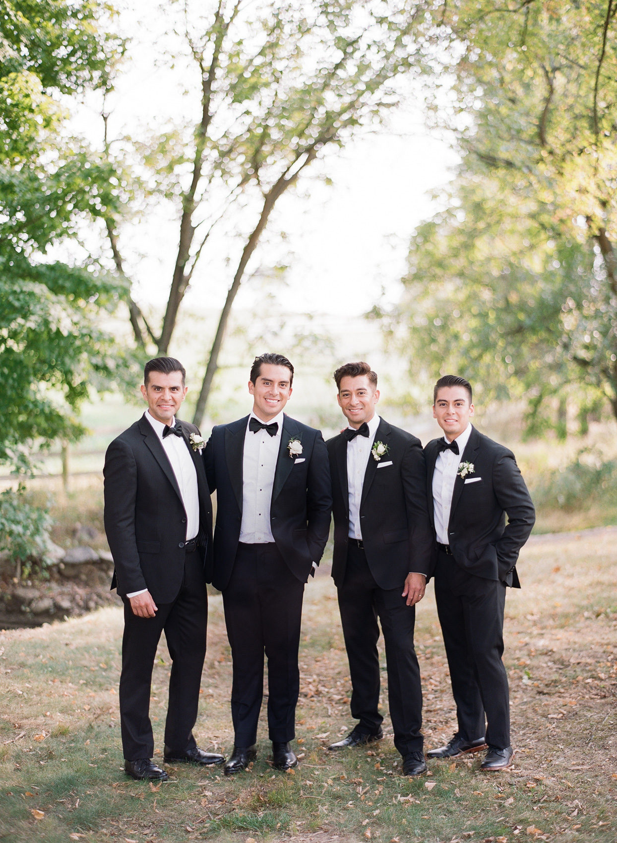 groom with three groomsmen in classic black suits