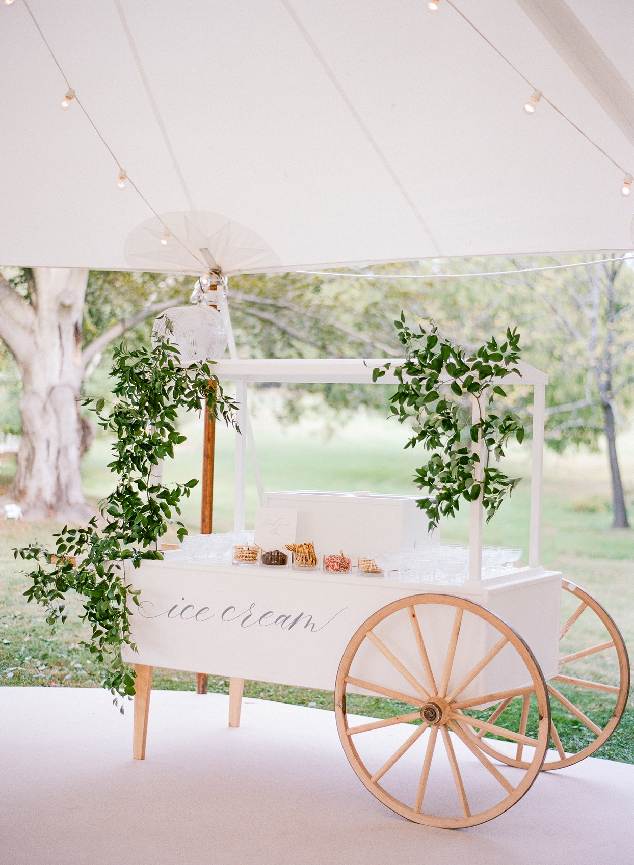 ice cream cart with greenery under reception tent
