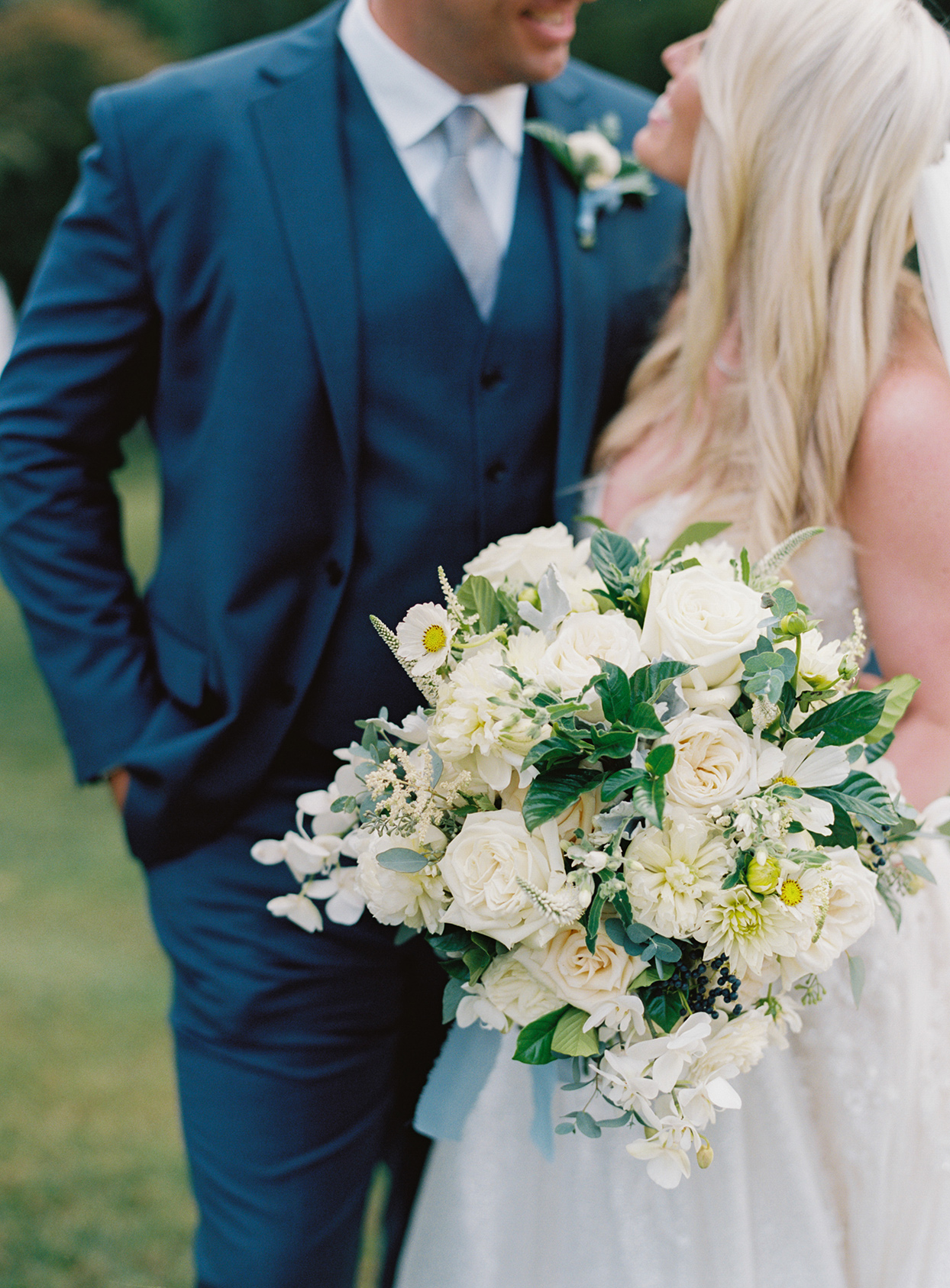 lauren chris couple standing together while bride holds white wedding bouquet