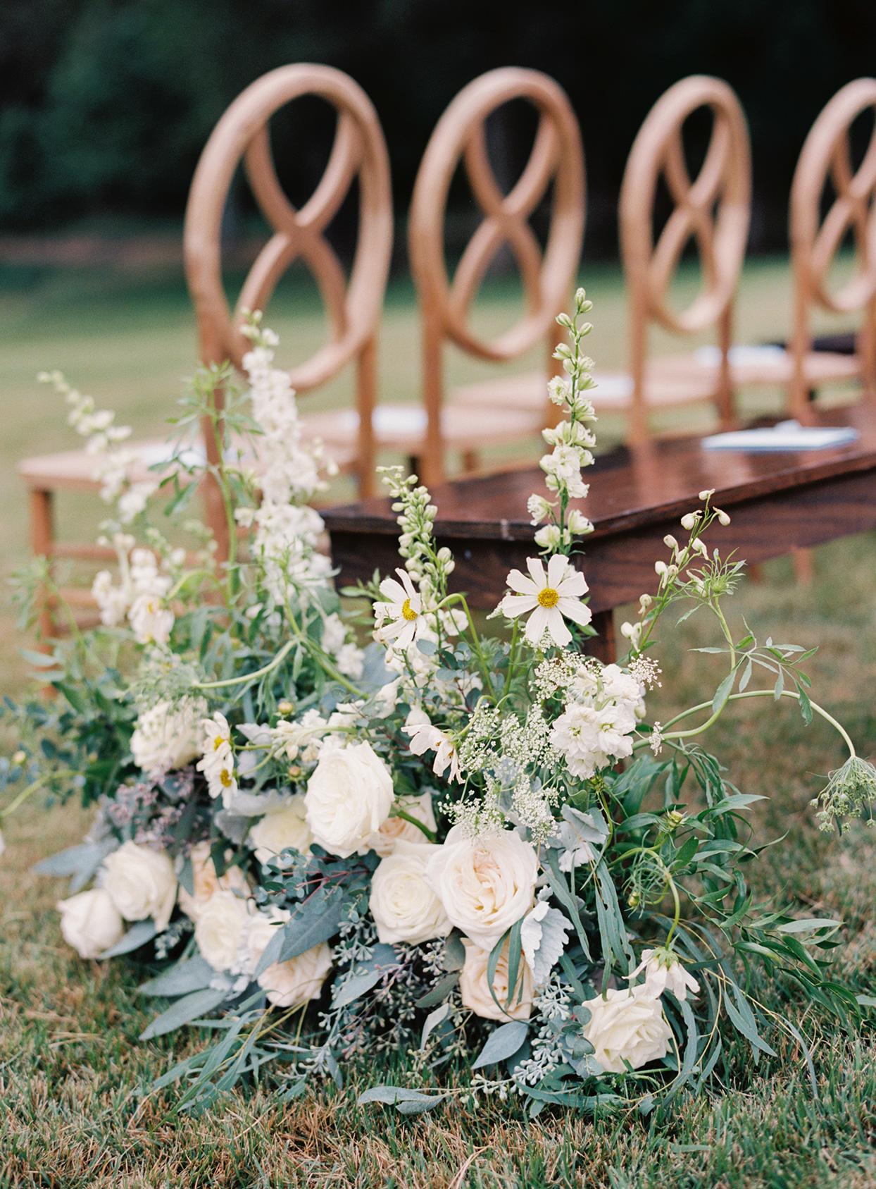 lauren chris wedding ceremony white flowers in the grass lining aisle