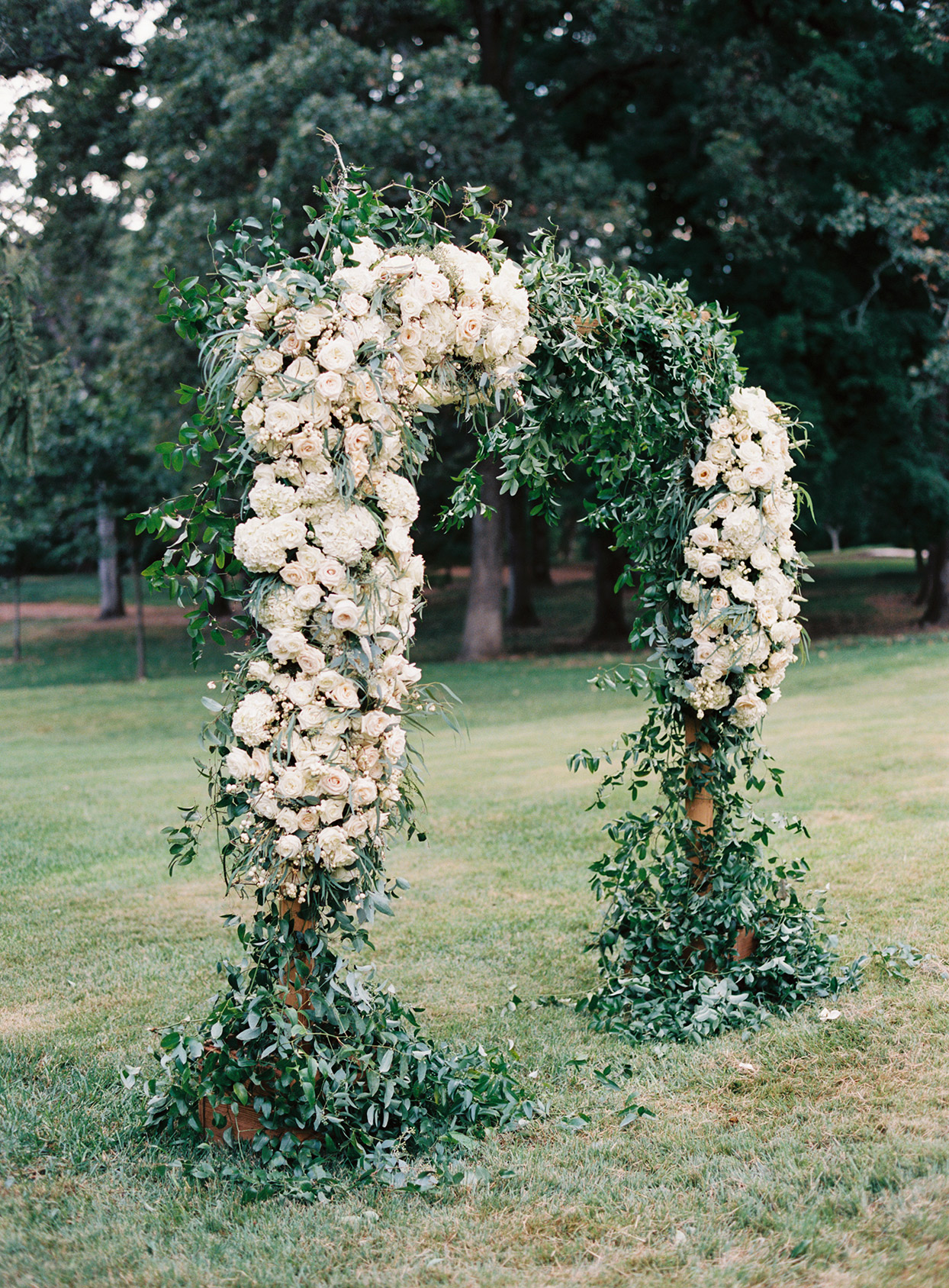 lauren chris wedding ceremony greenery and white roses arch in grass