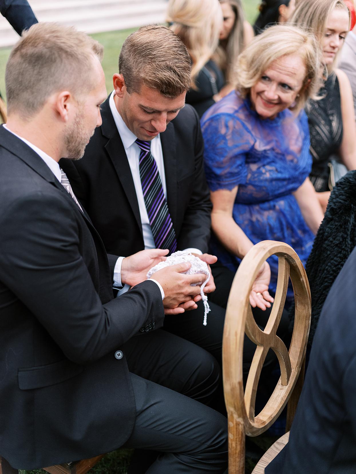 lauren chris wedding ceremony men holding bag of rings to warm them